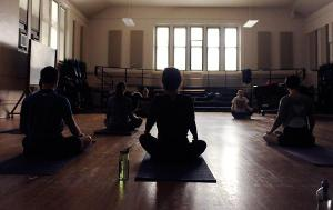 Grace Lyden turns off the lights and plays soothing instrumental music for her restorative yoga for musicians class. Lyden's class includes moves that specifically help musicians relieve stress.